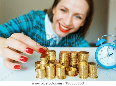 Saving smiling woman stacking gold coins into columns