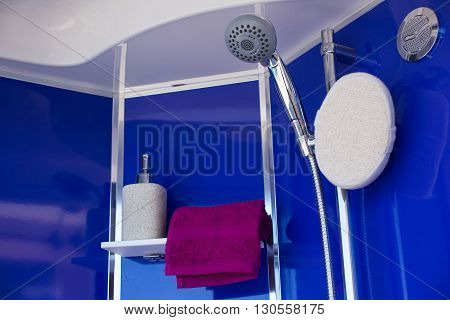 View of towel liquid soap and shower head
