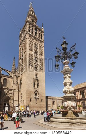 Seville, Spain - May 1, 2016: La Giralda, the bell tower of Seville Cathedral and the fountain on Plaza de Triunfo. Tourists all around the square.