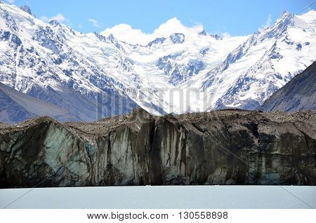 Glacier at the foot of snow covered mountains