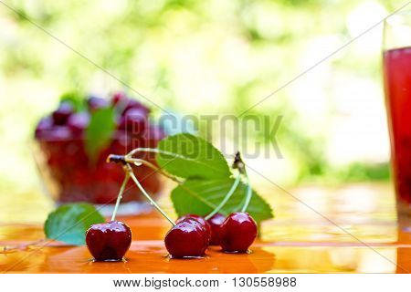 red cherry with bowl and juice on the table