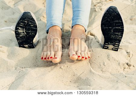 Bare female feet on the sand next to the shoes on the beach