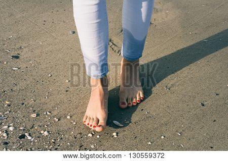 Bare Female Feet Walking On Wet Sand At Beach