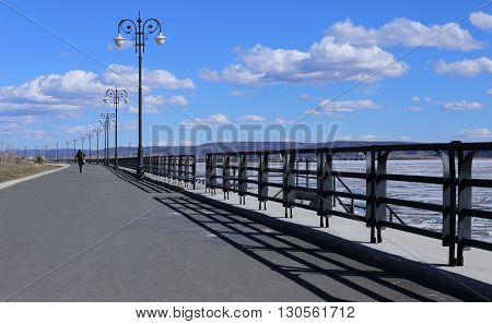 empty pier and calm water on a background of blue sky and clouds. beautiful fence and pillars. Woman goes forward