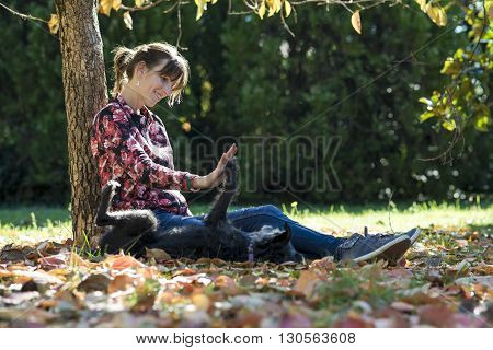 Happy young woman sitting under an autumn tree in a park playing with her black dog which is lifting its paw towards her.