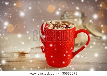 A cup of tasty cocoa and marshmallow on the table with snow effect