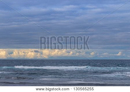 Morning view of the ocean with waves and beautiful clouds, blurred background of blue sky in Victoria, Australia