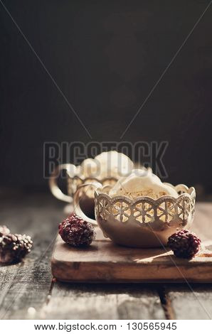 Two portions of delicious caramel ice cream  in bowls and dark brown on a wooden board .Toned photo