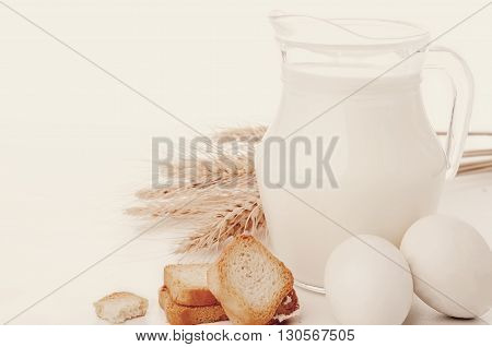 Glass jug with milk, wheat seeds and two eggs on white background .Toned photo