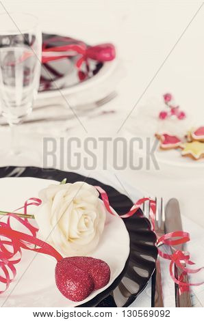 Holiday romantic table setting with pink roses on a white background .Toned photo