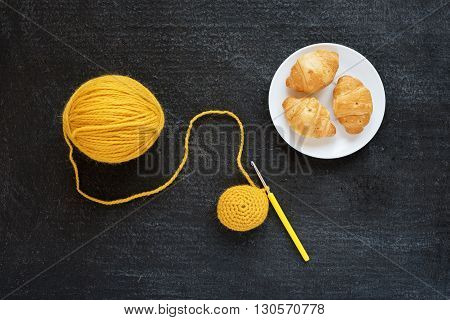 Yellow crocheting and croissants on black background
