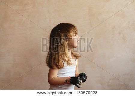 Little smiling girl with long hair and dirty hands on a shabby background