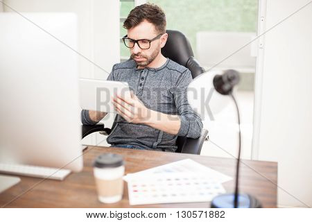 Young man with a beard and wearing glasses using a tablet computer while sitting at his desk at work