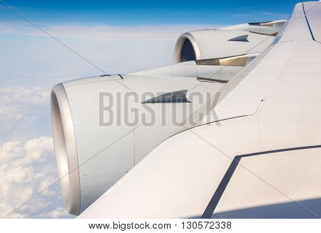 Wing with engines of Airbus A380 airliner flying over clouds