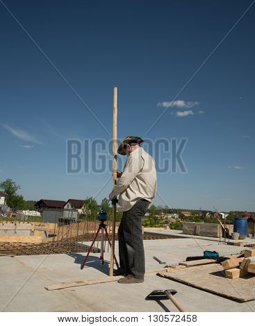Men is measuring height level of the building foundation with special equipment