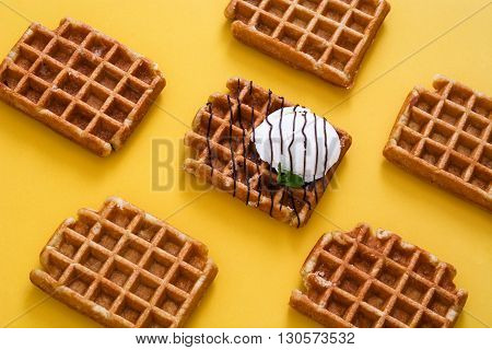 Waffles with chocolate sauce, ice cream and mint on yellow background