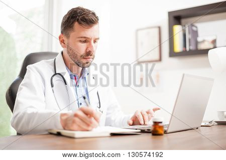 Young Doctor Taking Notes And Using A Laptop
