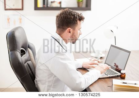 Doctor In Lab Coat Working On A Laptop