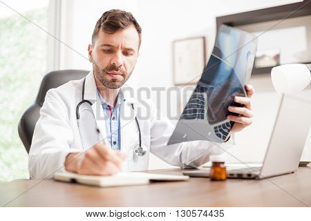 Doctor Taking Notes From Some X-rays