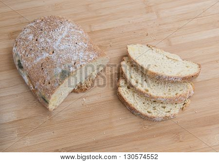 Piece and slices of unhealthy moldy bread on a wooden board