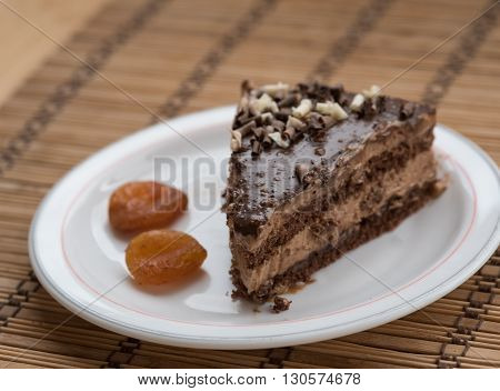 Slice of chocolate cake garnished with nuts on a plate with dry fruits.
