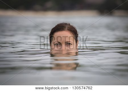 Portrait of a young woman in sea water. Close up