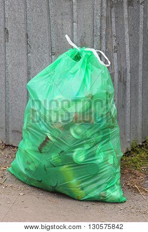 Green Bin Bag With Garbage at Street