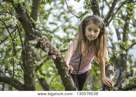 Little girl in headphones, in the branches of a tree.