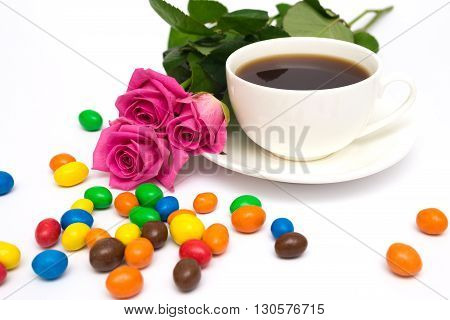 Cup of coffee, candies and pink roses