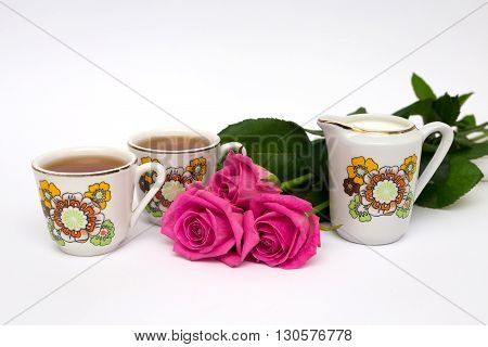 Two cups of tea and pink roses