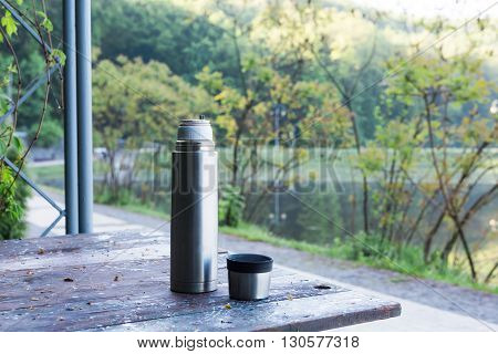 Thermos  And Cup Of Coffee On Wooden Table