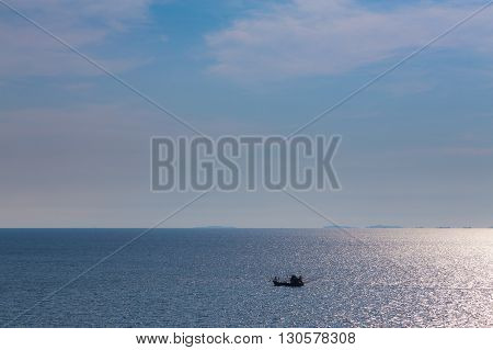 Small lonely boat in the big ocean, natural skyline background