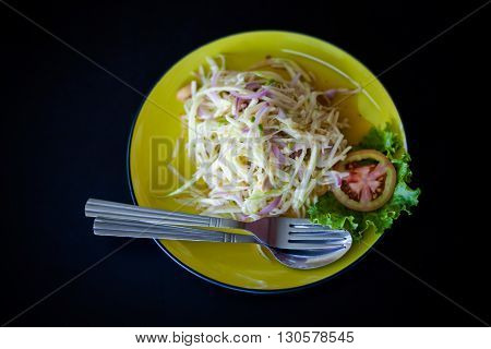 Fresh made hot papaya salad Som Tam with red onion and tomatoe. Traditional thai cuisine.