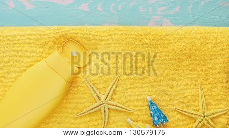 Summer holiday background. Summer background with sea shells and suntan lotion on beach towel. Top view, vintage toned image, blank space