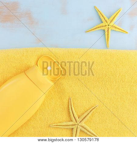 Summer vacation background. Summer background with sea shells and suntan lotion on beach towel. Top view, vintage toned image, blank space