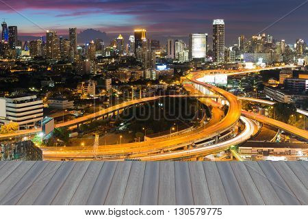 Opening wooden floor, City highway interchanged and downtown background night view