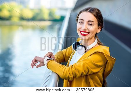 Young sport woman in yellow sweater looking at smart watch on the modern bridge with skyscrapers on the background. Morning exercise in megacity