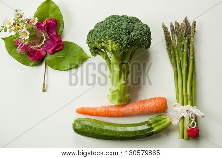 flat lay bgreen vegetables with yellow carot on white background
