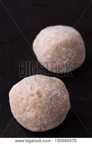 Torrone e Cannoli sicilian - italian nougat-balls on black slate background