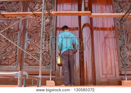 THAILAND LOEI PROVINCE MAY 06 2016 : Painters were painting on a wooden carving on the temple walls at Wat Somdej Phu Ruea Ming Muang in Loei province Thailand