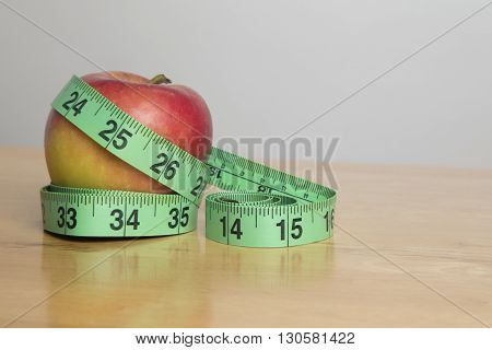 Green tape measure wrapped around an apple