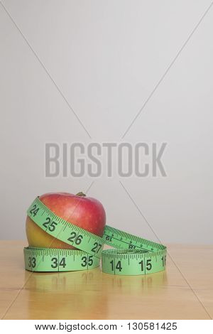 Green measuring tape wrapped around an apple