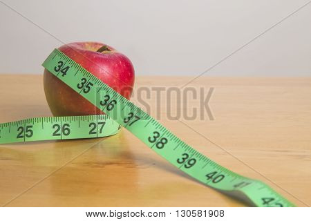 Green measuring tape around apple - health concept
