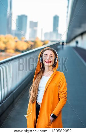 Young female music lover in yellow sweater listening to the music on the modern bridge with skyscrapers on the background.