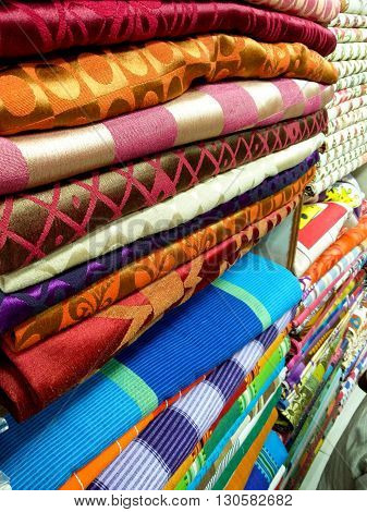 Folded sheets of fabric with various prints and designs. These are typically used for making tailored garments
