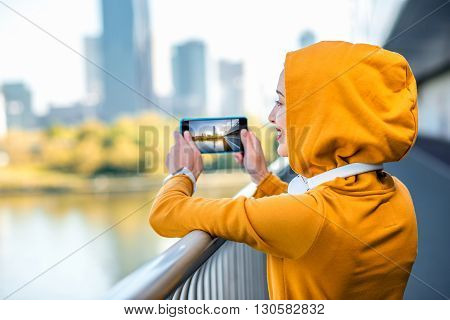 Young woman in yellow hood photographing modern city on the  bridge with skyscrapers on the background in the morning