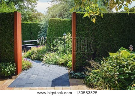 Sitting area in the garden enclosed by hedges.