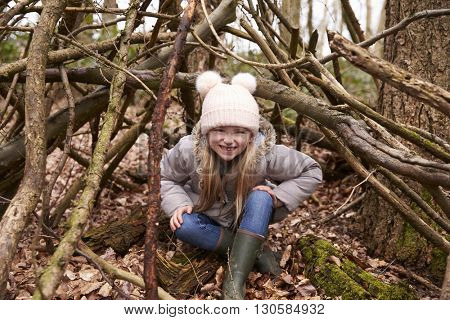 Young girl sits under shelter of tree branches, full length