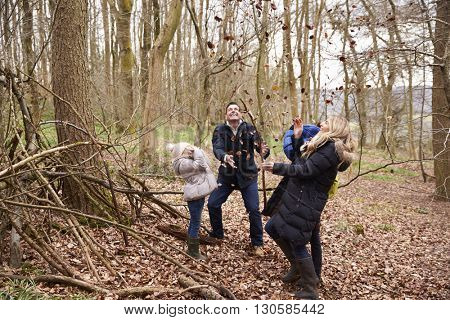 Family playing with fallen leaves in a wood, full length