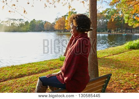 Woman listening music in the autumn park at sunset with headphones
